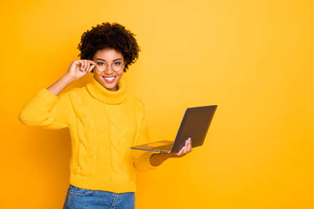 Foto de Photo of charming cute black curly attractive girlfriend holding her laptop and spectacles searching for something getting likes wearing jeans denim yellow pullover isolated vivid color background - Imagen libre de derechos