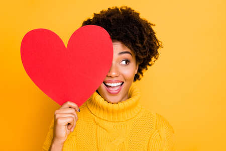 Photo pour Photo of trendy cheerful cute nice charming curly fascinating girlfriend looking out away from red big heart wearing yellow jumper while isolated with bright color background - image libre de droit