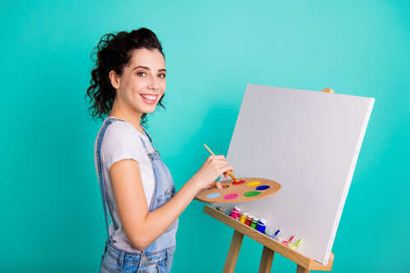Foto de Profile side view portrait of nice attractive creative cheery wavy-haired girl wearing casual holding in hands water color drawing new picture isolated on bright vivid shine green turquoise background - Imagen libre de derechos
