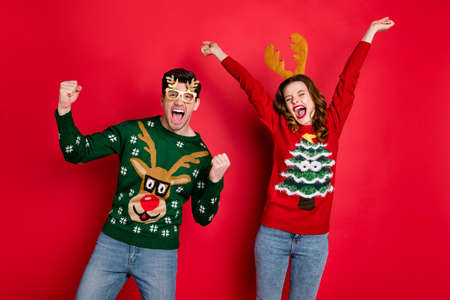 Portrait of crazy funny two lovers people wife husband brown hair celebrate victory raise fists scream yes wear christmas tree clothes eyeglasses jeans isolated over red color background