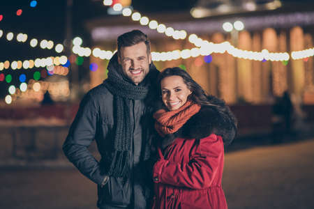 Photo for Photo of two sweethearts pair in love attending city park at newyear, midnight frosty weather standing close wearing warm winter jackets outdoors - Royalty Free Image