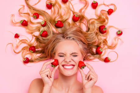Close up top above high angle view photo beautiful she her lady lying down among fruit strawberries long hair strong action of facial fruit scrub mask cream moisturizer lotion isolated pink background