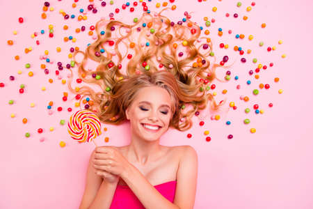 Photo for Vertical side profile top above high angle view photo she her lady lying down sweets ideal hair chocolate colored little candies arms hands lolly pop eyes closed imagination isolated pink background - Royalty Free Image