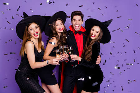 Photo pour Photo of witch ladies and wizard guy at helloween event drink golden wine glitter flying in air wear black dresses caps suit and long coat isolated purple color background - image libre de droit