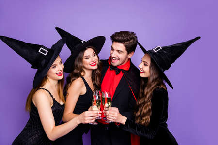 Foto de Photo of three excited witch ladies and warlock guy chilling at halloween party drink golden wine wear black dresses hats and vampire coat isolated purple color background - Imagen libre de derechos