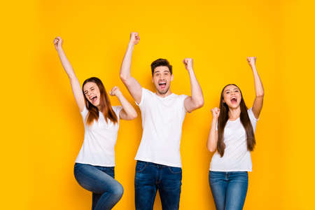 Photo pour Portrait of three nice attractive lovely cheerful cheery person celebrating cool attainment having fun rising hands up isolated over bright vivid shine yellow background - image libre de droit