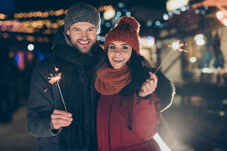 Photo pour Photo of funny couple at x-mas celebration in park holding magic sparklers excited to meet newyear midnight wearing warm coats knitted caps and scarfs outdoors - image libre de droit