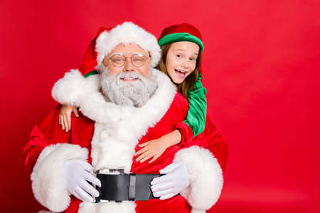 Photo pour Close up photo of charming santa claus in eyeglasses eyewear and his little elf helper in green hat headwear hugging piggyback isolated over red background - image libre de droit