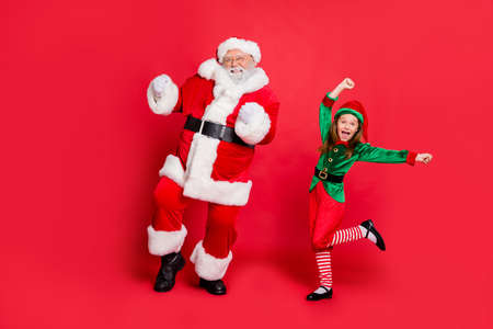 Foto de Full body photo of excited two santa claus in hat headwear dancing on festive event wearing green bright costume isolated over red background - Imagen libre de derechos