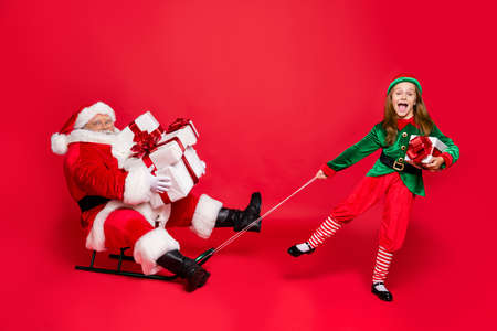 Foto de Full size photo of funny santa claus with eyeglasses eyewear spectacles and cute elf in green hat headwear holding sledges carry sack bag with gifts isolated over red background - Imagen libre de derechos