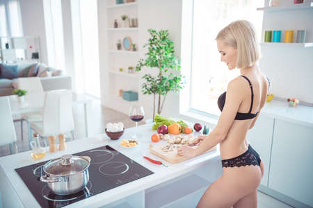 Foto de Profile side view of her she nice-looking attractive stunning sporty cheerful cheery girl making homemade tasty yummy delicious dish in modern light white interior kitchen indoors - Imagen libre de derechos