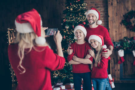 Photo for Photo of mom making photo of two children and daddy near decorated garland newyear tree indoors family x-mas atmosphere wear santa caps and red sweaters - Royalty Free Image