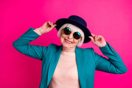 Photo pour Close-up portrait of her she nice attractive fascinating well-dressed cheerful gray-haired lady touching hat enjoying weekend isolated on bright vivid shine vibrant pink fuchsia color background - image libre de droit