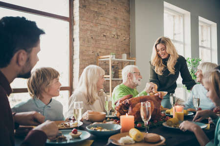 Photo of big full family reunion gathering sit feast dishes dinner table young wife giving old parents fresh bakery multi-generation in evening living room indoors