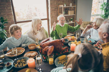 Photo pour Photo of full family reunion gathering sit feast dishes chicken table communicating fall november autumn holiday multi-generation in evening living room indoors - image libre de droit