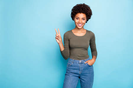 Photo pour Photo of toothy cute sweet attractive african girlfriend showing you v-sign, wearing jeans denim holding hand in pocket standing confidently isolated over blue vivid color background - image libre de droit