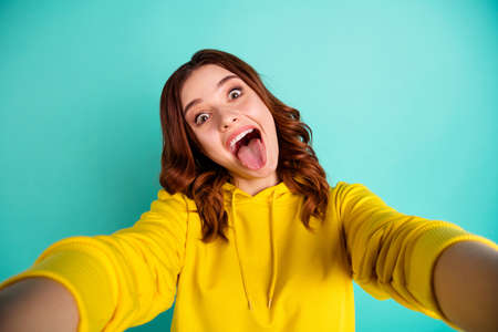 Photo pour Photo of curly wavy charming nice cute sweet pretty girlfriend in trip showing you tongue out with overjoyed facial expression taking selfie in yellow sweater isolated over teal vivid color background - image libre de droit
