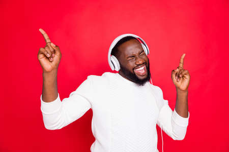 Photo pour Photo of amazing dark skin man listening favorite playlist in earflaps enjoy best song moment rhythm wear white knitted sweater isolated red background - image libre de droit