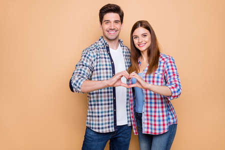 Photo pour Portrait of his he her she nice attractive charming tender cheerful couple wearing checked shirt embracing showing heart figure honeymoon isolated over beige pastel color background - image libre de droit