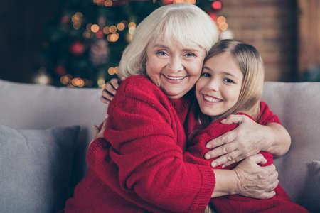 Photo pour Close-up portrait of nice attractive lovely sweet glad tender affectionate cheerful cheery granny grandchild sitting on cosy divan hugging tradition at decorated industrial loft style interior house - image libre de droit