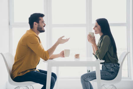 Photo pour Profile photo of handsome guy and his pretty lady looking tender eyes drinking hot beverage sitting chairs opposite in modern interior light cafe indoors wear casual clothes - image libre de droit