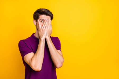 Photo for Portrait of his he nice attractive scared guy wearing violet shirt hiding face in palms peeking isolated on bright vivid shine vibrant, yellow color background - Royalty Free Image