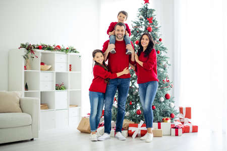 Foto de Full body photo of big full lovely family of schoolgirl cuddle her daddy carry younger child and mommy celebrate christmas time x-mas holidays in house with gifts indoors - Imagen libre de derechos