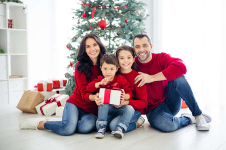 Foto de Full body photo of big full charming dad mom schoolgirl small boy holding package for christmas night enjoy x-mas having brunet hair wearing red pullover denim jeans in house indoors - Imagen libre de derechos