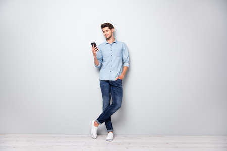 Foto de Full size photo of concentrated smm worker man use cellphone answer sms messages have online conversation with friends type comments posts wear stylish outfit sneakers isolated grey color background - Imagen libre de derechos