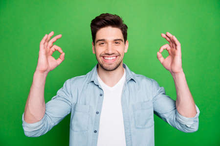 Photo of cheerful attractive handsome bearded man smiling toothily showing you double ok sign isolated over green vivid color background