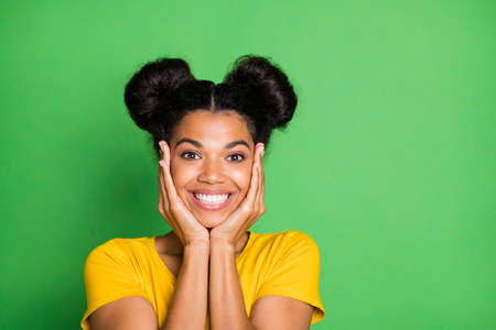 Photo pour Closeup photo of pretty dark skin lady holding arms on cheeks having best weekend mood toothy smiling wear casual yellow t-shirt isolated green background - image libre de droit