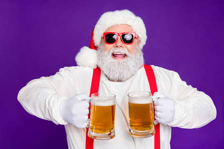 Photo pour Close-up portrait of nice glad cheerful cheery positive bearded Santa holding in hands two mugs drinking beer having fun isolated over bright vivid shine vibrant violet lilac background - image libre de droit