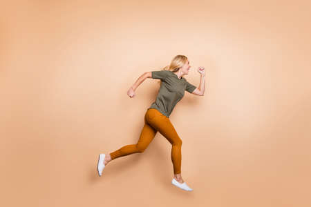 Photo pour Full length profile photo of crazy lady jumping high speed race marathon participant competitive mood rushing sales wear green t-shirt yellow trousers isolated beige color background - image libre de droit