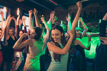 Photo for Portrait of positive cheerful elegant girlfriends crowd people celebrate noel party dance on discotheque have fun feel rejoice wearing formalwear dress in green neon lights - Royalty Free Image