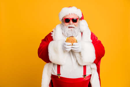 Photo for Portrait of funny funky fat santa claus dont care about health eat fast food big sandwich on x-mas tradition celebration wear style stylish suspenders isolated over shine color background - Royalty Free Image