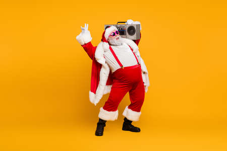 Photo for Full length photo of funny fat santa claus hipster with big belly hold boombox have fun listen christmas carols celebrate x-mas noel party wear red hat headwear boots isolated yellow color background - Royalty Free Image
