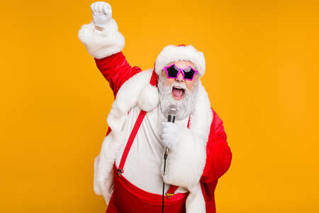 Photo for Grey haired stylish christmas grandfather in red hat cap celebrate x-mas party hold microphone sing noel carols feel funky with big belly wear suspenders isolated over yellow color background - Royalty Free Image
