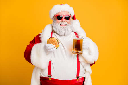 Photo pour Portrait of funny funky santa claus with big belly want relax rest on x-mas celebration party hold glass of beer meat sandwich wear stylish suspenders red hat headwear isolated yellow color background - image libre de droit