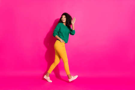 Photo for Full length profile side photo of positive curly hair afro american girl had fun on winter free time go walk hold hand say bye wear knitted jumper outfit pants sneakers isolated pink color background - Royalty Free Image