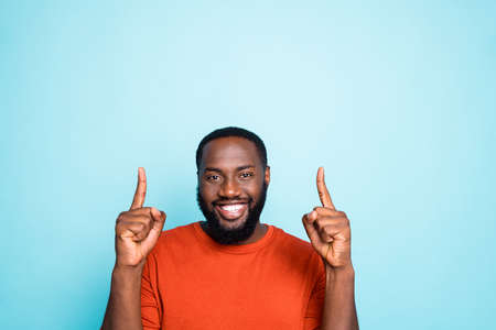 Photo pour Close up photo of attractive dark skin guy indicating fingers up empty space, advising nice low sale prices wear casual orange pullover isolated blue color background - image libre de droit