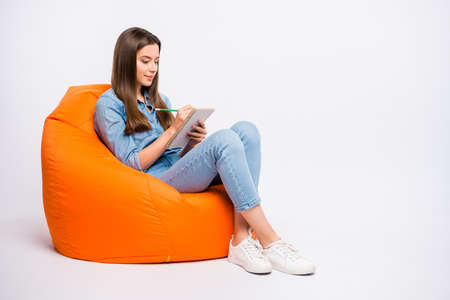 Photo pour Full size profile side photo of concentrated girl write in copybook her homework for tomorrow lesson in university sit big bag armchair wear casual style clothes isolated over white color background - image libre de droit