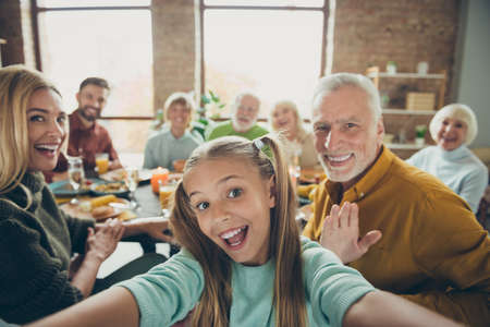 Photo pour Video call from happy big family celebrate thanksgiving day october autumn event party small little girl kid make selfie mature grandfather say hi wave hand grandmother enjoy meal in house - image libre de droit