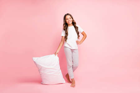 Foto de Full length body size view of her she nice attractive cute sweet lovely cheerful wavy-haired pre-teen girl carrying holding in hands white soft pillow isolated on pink pastel color background - Imagen libre de derechos