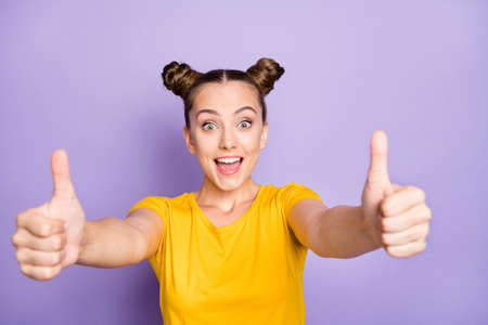 Photo pour Photo of pretty teenager lady raising thumbs up expressing agreement and positive attitude wear yellow t-shirt isolated on pastel purple background - image libre de droit
