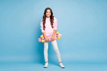 Photo pour Full length body size photo of cheerful positive pink schoolchild holding skateboard smiling cheerfully isolated pastel blue color background - image libre de droit
