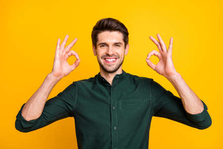 Photo of cheerful kind handsome man showing you double ok sign smiling toothily with bristle isolated over yellow vibrant color background