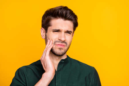 Ouch. Close up photo of upset sad guy feel ill suffer from disease toothache touch his cheek face cry need medical dentistry treatment wear casual style clothing isolated over yellow color background