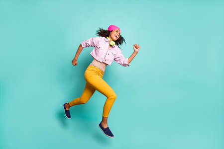 Foto de Turned full length body size photo of casual positive running jumping girl aspiring for discounted goods wearing yellow pants trousers pink jacket striped t-shirt isolated teal color background vivid - Imagen libre de derechos