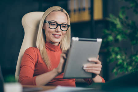 Photo pour Perfect leader big company owner charming woman sit chair table use tablet search modern start-up development news employee training in office loft wear red turtleneck - image libre de droit