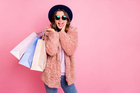 Foto de Photo of pretty lady hold carry many packs shopper tourism abroad look unbelievable sale prices hand on cheek store wear jacket sun specs hat jeans isolated pink background - Imagen libre de derechos